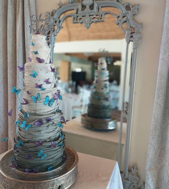 *#&!✓? FINALLY!  ... Check out this showstopper! I don't think I could even calculate how many strips of fondant I wrapped around the 5 tiers of this salted caramel cake!  ... The ombre grey look matched the interior of @hudsonsvenue perfectly - cakes always looks spectacular infront of that huge mirror ... The butterfly theme was incorporated throughout the venue, and I used delicate little wafer paper butterflies from @crystalcandysa. Just a note - I ordered them from Jozi late in the afternoon, and they were delivered the next morning before 10am in Cape Town. Incredible service - thank you! ... The super cool topper came from my friends at @creatif_helderberg  ... #weddingcake #weddingcakes #cakesbycrumb #cakeme #cake #weddingcakesofinstagram #cakeoftheday #crumb #crumbcakessa #weddingcakescapetown #cakedecorating