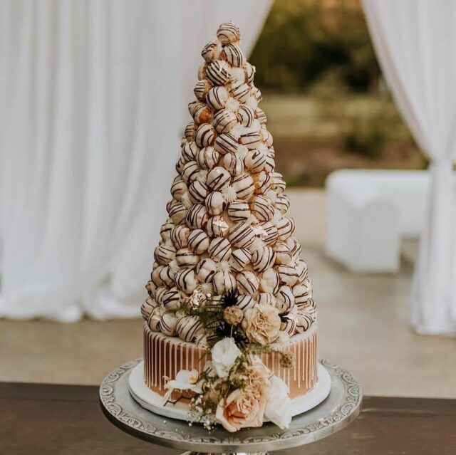 CROQUEMBOUCHE! ... A an school French classic - but there's nothing wrong with that!  How gorgeous is this photo of this croccie we did at @molenvliet_vineyards just before the autumn kicked in?  ... I've had a few enquiries for these recently, so maybe these beauties are making a comeback? Would love to do a few way out colourful ones too!  ... Thanks @agp_annegracephotography for the exquisite photo, and to @strawberryweddingsandevents for including us in this stunning celebration ... #weddingcakesofinstagram #weddingcakes #weddings #croquembouche #crumbcakes #crumb #cakedecorator #choux #chouxbuns #cake #cakeotd #molenvliet